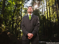 Picture of a man standing in the woods with his hands clasped in front of him and looking up.  Low camera angle looking up at man. Close up portrait if a businessman wearing a green necktie and a business suit in the middle of the forest.